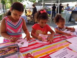 Children coloring a craft at the Farmers Market